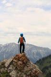 Viaggiatore con zaino e sacco a pelo che fa un'escursione sulla scogliera del picco di montagna Fotografia Stock