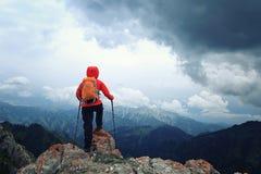 Viaggiatore con zaino e sacco a pelo che fa un'escursione sulla scogliera del picco di montagna Fotografie Stock
