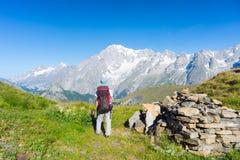 Viaggiatore con zaino e sacco a pelo che fa un'escursione sulle alpi, Mont Blanc maestoso nel fondo Fotografie Stock Libere da Diritti