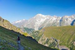 Viaggiatore con zaino e sacco a pelo che fa un'escursione sulle alpi, Mont Blanc maestoso nel fondo Fotografia Stock Libera da Diritti