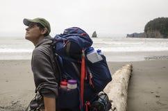 Viaggiatore con zaino e sacco a pelo che guarda fisso su alla spiaggia Fotografia Stock Libera da Diritti