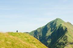 Viaggiatore con zaino e sacco a pelo che scala alla cima della montagna Immagini Stock Libere da Diritti