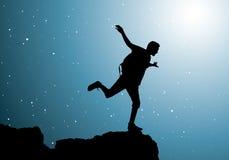Viaggiatore con zaino e sacco a pelo che si leva in piedi in cima alla montagna Immagini Stock