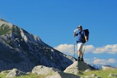 Viaggiatore con zaino e sacco a pelo che si leva in piedi su una roccia Fotografia Stock Libera da Diritti