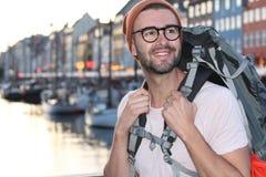 Viaggiatore con zaino e sacco a pelo che sorride nel Nyhavn epico, Copenhaghen, Danimarca Immagini Stock Libere da Diritti