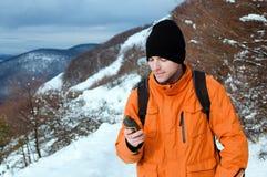 Viaggiatore con zaino e sacco a pelo che tiene GPS Immagini Stock Libere da Diritti