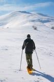 Viaggiatore con zaino e sacco a pelo che va nevicare montagna Fotografia Stock