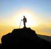 Viaggiatore con zaino e sacco a pelo con il bastone da passeggio nel tramonto Immagini Stock Libere da Diritti