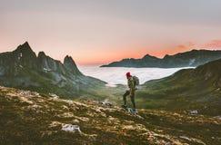 Viaggiatore con zaino e sacco a pelo dell'uomo che fa un'escursione in montagne da solo all'aperto fotografia stock libera da diritti