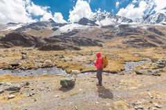 Viaggiatore con zaino e sacco a pelo dell'uomo che fotografa la corrente del fiume della montagna del lama Immagine Stock