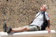 Viaggiatore con zaino e sacco a pelo dell'uomo senior che riposa all'aperto Fotografia Stock