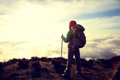 Viaggiatore con zaino e sacco a pelo della donna al picco di montagna di alba Immagini Stock Libere da Diritti