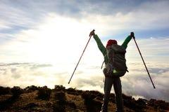 Viaggiatore con zaino e sacco a pelo della donna al picco di montagna di alba Fotografia Stock