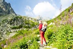 Viaggiatore con zaino e sacco a pelo della donna in alto Tatras Fotografia Stock