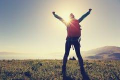 Viaggiatore con zaino e sacco a pelo della donna a braccia aperte sul picco di montagna Fotografie Stock Libere da Diritti