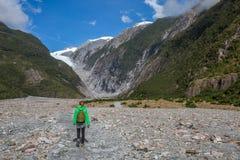 Viaggiatore con zaino e sacco a pelo della donna che cammina in Franz Josef Glacier fotografia stock