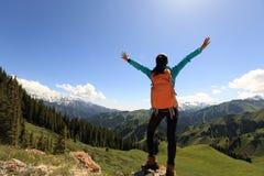 Viaggiatore con zaino e sacco a pelo della donna che fa un'escursione a braccia aperte sul picco di montagna della foresta Fotografia Stock Libera da Diritti