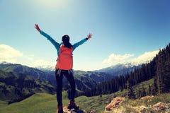 Viaggiatore con zaino e sacco a pelo della donna che fa un'escursione a braccia aperte sul picco di montagna della foresta Fotografia Stock