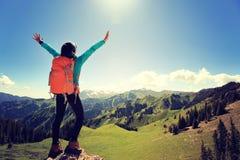 Viaggiatore con zaino e sacco a pelo della donna che fa un'escursione a braccia aperte sul picco di montagna della foresta Immagini Stock Libere da Diritti