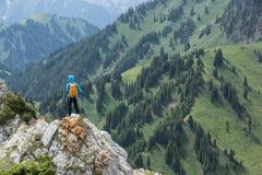 Viaggiatore con zaino e sacco a pelo della donna che fa un'escursione sul picco di montagna Fotografie Stock Libere da Diritti