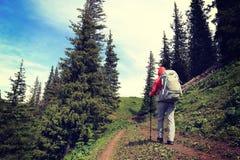 Viaggiatore con zaino e sacco a pelo della donna che fa un'escursione sulla bella traccia del picco di montagna Fotografia Stock