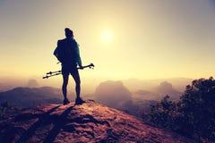 Viaggiatore con zaino e sacco a pelo della donna che fa un'escursione sulla cima della montagna di alba Immagini Stock