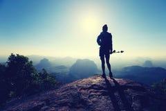 Viaggiatore con zaino e sacco a pelo della donna che fa un'escursione sulla cima della montagna di alba Fotografie Stock