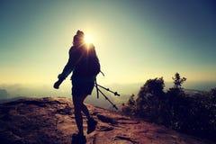 Viaggiatore con zaino e sacco a pelo della donna che fa un'escursione sulla cima della montagna di alba Fotografia Stock