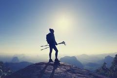 Viaggiatore con zaino e sacco a pelo della donna che fa un'escursione sulla cima della montagna di alba Immagine Stock Libera da Diritti