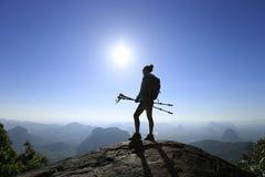 Viaggiatore con zaino e sacco a pelo della donna che fa un'escursione sulla cima della montagna di alba Immagini Stock Libere da Diritti