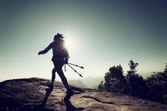 Viaggiatore con zaino e sacco a pelo della donna che fa un'escursione sulla cima della montagna di alba Fotografia Stock Libera da Diritti