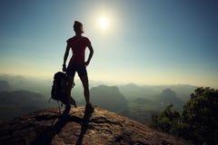 Viaggiatore con zaino e sacco a pelo della donna che fa un'escursione sulla cima della montagna di alba Immagine Stock