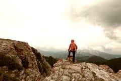 Viaggiatore con zaino e sacco a pelo della donna che fa un'escursione sulla scogliera del picco di montagna Fotografie Stock Libere da Diritti