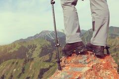 Viaggiatore con zaino e sacco a pelo della donna che fa un'escursione sulla scogliera del picco di montagna Immagine Stock Libera da Diritti