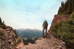 Viaggiatore con zaino e sacco a pelo della donna che fa un'escursione sulla scogliera del picco di montagna Fotografia Stock Libera da Diritti