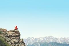 Viaggiatore con zaino e sacco a pelo della donna che fa un'escursione sulla scogliera del picco di montagna Immagini Stock Libere da Diritti