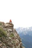 Viaggiatore con zaino e sacco a pelo della donna che fa un'escursione sulla scogliera del picco di montagna Immagine Stock