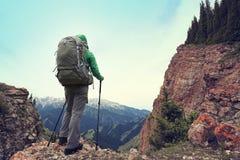 Viaggiatore con zaino e sacco a pelo della donna che fa un'escursione sulla scogliera del picco di montagna Immagini Stock