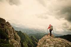Viaggiatore con zaino e sacco a pelo della donna che fa un'escursione sulla scogliera del picco di montagna Fotografie Stock