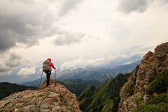 Viaggiatore con zaino e sacco a pelo della donna che fa un'escursione sulla scogliera del picco di montagna Fotografia Stock