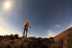 Viaggiatore con zaino e sacco a pelo della donna che scala al picco di montagna Immagine Stock