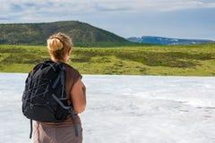 Viaggiatore con zaino e sacco a pelo della donna negli altopiani un giorno di estate Immagine Stock Libera da Diritti