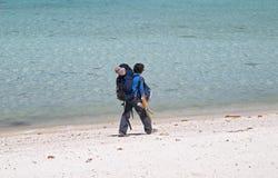 Viaggiatore con zaino e sacco a pelo della ragazza che cammina su una spiaggia fotografia stock libera da diritti