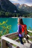 Viaggiatore con zaino e sacco a pelo della ragazza che esamina il lago Braies Fotografia Stock
