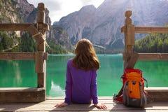 Viaggiatore con zaino e sacco a pelo della ragazza che esamina il lago Braies Fotografie Stock Libere da Diritti