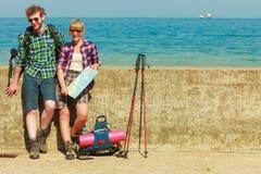 Viaggiatore con zaino e sacco a pelo delle coppie con la mappa dalla spiaggia Immagine Stock Libera da Diritti