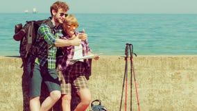 Viaggiatore con zaino e sacco a pelo delle coppie con la mappa dalla spiaggia Fotografia Stock Libera da Diritti