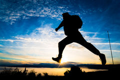 Viaggiatore con zaino e sacco a pelo di salto Immagine Stock