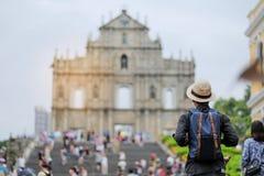 Viaggiatore con zaino e sacco a pelo di viaggio del giovane con il cappello, viaggiatore asiatico dei pantaloni a vita bassa che  immagine stock