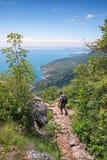 Viaggiatore con zaino e sacco a pelo a idyllec che fa un'escursione percorso sopra il lago di polizia Immagini Stock